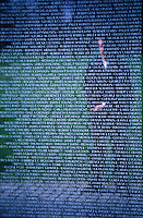 reflection of a man looking at The Vietnam Memorial in Washington, DC