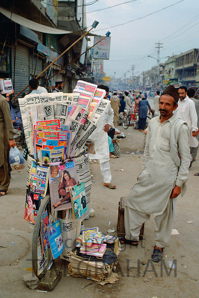 Man selling newspapers stacked on a bicycle in the streets of Islamabad in Pakistan