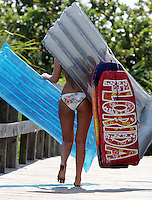 Rafts and boards partially cover a tourist as she makes her way to the beach in Cape Canaveral, Florida. Photo/Andrew Shurtleff
