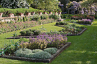 The rose garden at La Foce has flowerbeds shaped with stone and is lined with terracotta pots and wisteria