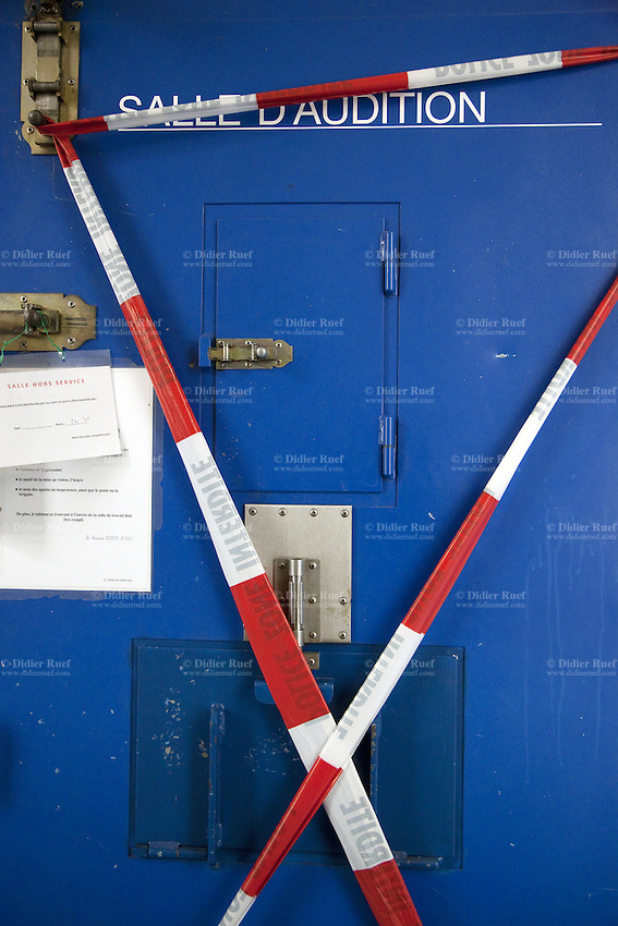 Switzerland. Geneva. Paquis police station. A red and white plastic police tape on a closed cell's door. Police line, Do not cross. The cell is lockeg because it has been been disinfected from its dirtiness ( urine, excrements or bloodstains). A police station or station house is a building which serves for police officers. The building contains temporary holding cells and interview/interrogation rooms. 15.05.12 © 2012 Didier Ruef
