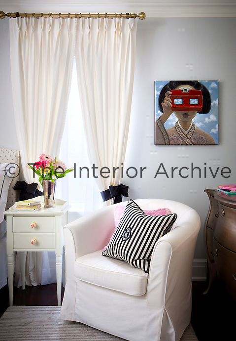 A child's bedroom in neutral tones. A tub chair stands in front of a painted chest of drawers.
