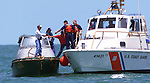 Five Cuban refugees board a U.S. Coast Guard vessel from their 22-foot boat west of Cape Romano, south of Marco Island, after being intercepted by Collier County sheriff's deputies on Tuesday. Erik Kellar/Staff..