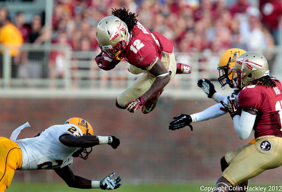 TALLAHASSEE, FL 9/1/12-FSU-MURRAY090112CH-Florida State's Jarred Haggins, center, goes airborne between Murray State's Darrian Skinner, left, and Corey Addison as FSU's Greg Dent blocks Addison during first half action Saturday at Doak Campbell Stadium in Tallahassee. .COLIN HACKLEY PHOTO