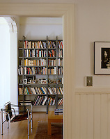 The stainless steel frame of a Le Corbusier chair relates to the uprights of the metal floor-to-ceiling bookcase in this glimpse into the library