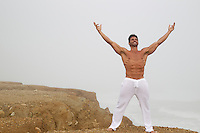 shirtless muscular man standing on a cliff in the fog with his arms open
