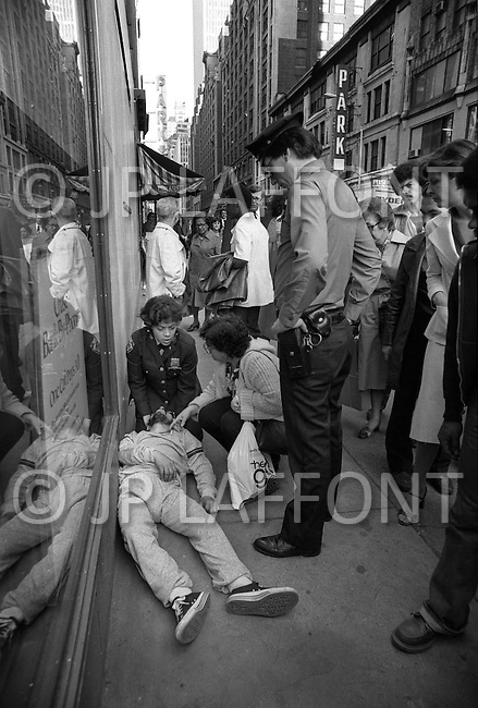 May, 1980. Manhattan, New York City, NY. Bystanders gather around two NYPD officers assisting a man suffering a drug overdose on a Times Square corner. It happens so often it does not stop the traffic.<br /> <br /> Manhattan, New York City, NY. Mai, 1980. Sur Times Square, des pi&eacute;tons regardent deux policiers qui viennent en aide &agrave; une victime d&rsquo;overdose, la sc&egrave;ne est si fr&eacute;quente qu&rsquo;elle n&rsquo;arr&ecirc;te plus le trafic.