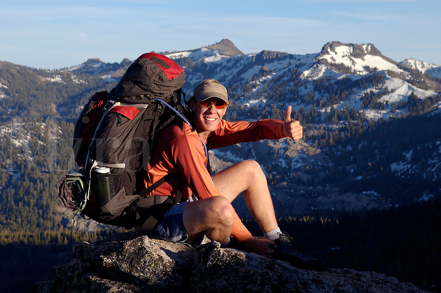 A man celebrating after reaching the summit of a mountain in the Sierras.
