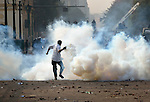 A demonstrator prepares to hurtle a smoking tear gas canister back at police during November 25, 2012, protests in and around Cairo's Tahrir Square. The protestors were upset by Egyptian President Mohammed Mursi's November 22nd decision to assume sweeping new powers.
