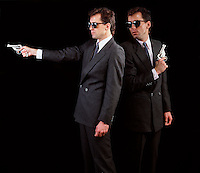 2 two twin mysterious men in black suits caucasian males duel w hand guns pistols copy space