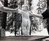 An adorable baby stands on a picnic table with the help of her parents.