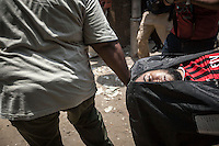 In this Monday, Jul. 08, 2013 photo, a dead person is wheeled to the morgue from Republican Guard heardquarters were got shot allegedly by Egyptian army forces in Cairo, Egypt. (Photo/Narciso Contreras).