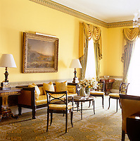 Detail of the antique sofa and chairs, re-upholstered in gold spotted satin, in the yellow drawing room
