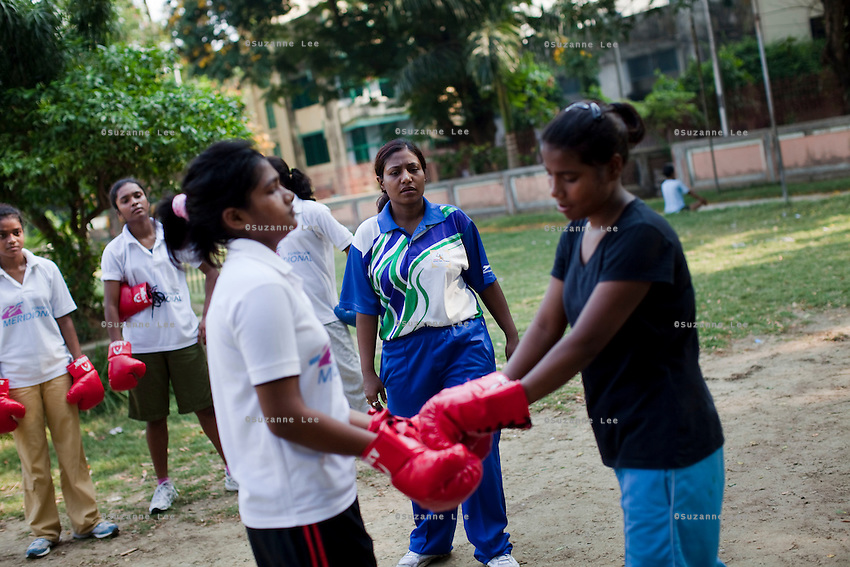 Trainees touch gloves before beginning their sparring session as Razia Shabnam (in blue) conducts a boxing training session with a group of girls from an NGO in a park in Basduni, Tolly Gunge, Calcutta, West Bengal, India. Razia Shabnam, 28, was one of the first women boxers in Kolkata. She was also the first woman in her community to go to college. She is now a coach and one of only three international female boxing referees in India.  Photo by Suzanne Lee for Panos London