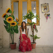 A Roma girl sits beside a plastic sunflower and a religious icon of Jesus Christ, in her home, in the old part fo Sintesti Roa camp..