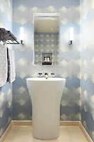 A tall pedestal washbasin is set beneath a mirror. The bathroom walls are covered in a blue and white patterned wallpaper.