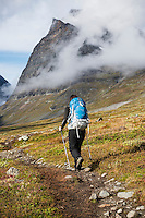 Female hiker on trail in Ladtjovagge with Tolpagorni - Duolbagorni mountain in distance, Lappland, Sweden