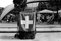 """Switzerland. Canton Ticino. Bellinzona. Piazza del Sole. A swiss flag and a podium with a microphone for a swiss army's speaker. A helmet and a camouflage lattice. People wait in front of the entrance of a Migros supermarket. Migros is Switzerland's largest retail company, its largest supermarket chain and largest employer. It is also one of the forty largest retailers in the world. It is structured in the form of a cooperative society (the Federation of Migros Cooperatives), with more than two million members. The name comes from the French """"mi"""" for half or mid-way and """"gros"""", which means wholesale. Thus the word connotes prices that are halfway between retail and wholesale. 11.04.2017 © 2017 Didier Ruef"""
