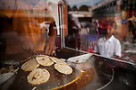 A vender cooks up tacos at a market in Nueva Concepcion, Guatemala, on Wednesday, Nov. 2, 2011. This rough town is also where narco traffickers pass through.
