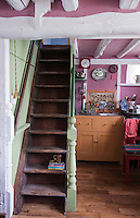 The compact kitchen is situated beneath the ladder staircase