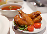 Chicken wings on a plate and soup at a cafe