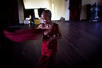 A novice monk quickly adjusts his robe.