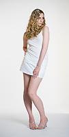Caucasian blonde woman posing towards camera on white seamless
