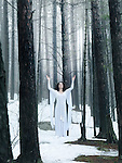 Woman in white dress standing in a middle of a forest with her arms raised to the sky. Spiritual concept. Wintertime outdoor scenery.