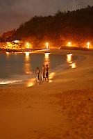 Three boys stand on the beach after sundown. Waimea bay on the North Shore of Oahu.