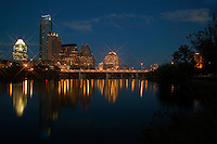 Austin Skyline at night with reflection on still waters of Town Lake from Auditorium Shores.
