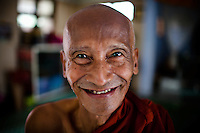 An elder monk in a small monastery emits a warm friendly smile.