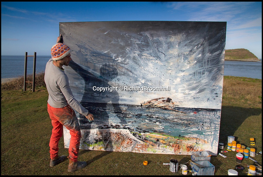 BNPS.co.uk (01202 558833)<br /> Pic: RichardBroomhall/BNPS<br /> <br /> Artist in Residence...Garratt in his element, at work on his Puffin Island canvas.<br /> <br /> Artist Anthony Garratt is giving a whole new meaning to landscape painting - his incredible pieces aren't just of the landscape, they're in it too.<br /> <br /> The 35-year-old painter from Bristol has created four canvasses on the island of Anglesey as part of a new outdoor art installation and the paintings will remain in the exact spot they were painted until October.<br /> <br /> Mr Garratt spent several days on each of the giant 8ft-wide scenes, which are exposed to the elements and can be enjoyed by walkers as well as art fans. <br /> <br /> The landscapes had to be created on marine board - a thick marine plywood treated with sealant and epoxy, like a boat - rather than normal canvas, coated with five layers of varnish afterwards and mounted on bespoke steel frames to ensure they survive any harsh outdoor conditions.