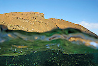 Bartolome Island rock and water surface (split shot half underwater), Ecuador, Galapagos Archipelago