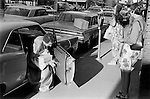 Ladies putting money in parking meter before going to the Casino wearing ball gown. Reno Nevada USA 1969