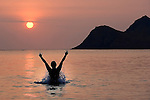 Person jumps up in ecstasy with the rising sun. The morning sun is a fireball from the volcanic fog (VOG).