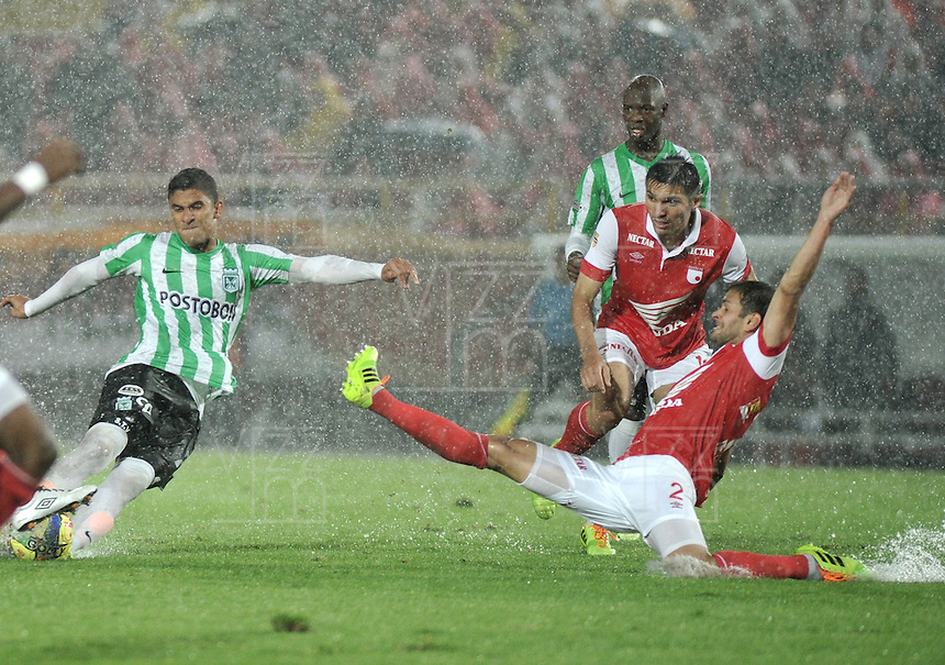 BOGOTA - COLOMBIA -07 -05-2014: Jose De La Cuesta (Der.) jugador de Independiente Santa Fe disputa el balón con Santiago Trellez (Izq.) jugador de Atletico Nacional, durante partido de ida entre Independiente Santa Fe y Atletico Nacional, por las semifinales de la Liga Postobon I-2014, jugado en el estadio Nemesio Camacho El Campin de la ciudad de Bogota./ Jose De La Cuesta (R) player of Independiente Santa Fe struggles for the ball Santiago Trellez (L) player of Atletico Nacional, during a match for the first leg between Independiente Santa Fe and Atletico Nacional, for the semifinals of the Liga Postobon I -2014 at the Nemesio Camacho El Campin Stadium in Bogota city, Photos: VizzorImage  / Luis Ramirez / Staff.