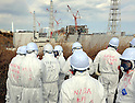 February 20, 2012, Fukushima, Japan - Members of the media, TEPCO, and the Nuclear and Industrial Safety Agency (NISA), wearing protective suits and masks, look at the tsunami-damaged Fukushima No. 1 Nuclear Power Plant's, from left to right, No. 1, 2, 3 and 4 reactor buildings on Feb. 20, 2012, in Okuma, Fukushima Prefecture.