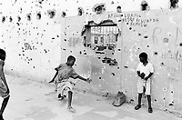 Angola. Province of Bié. Kuito. The town was heavily destroyed in 1993-1994 and 1998-1999 due to the intense civil war between the Government and Unita. Bullet and gun holes on the building's wall. Children play football with a ball made out of tissues tied together with a rope. © 2000 Didier Ruef