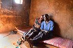 In northern Uganda,  a farmer and his wife relax in the bedroom of their new concrete home.   The solid structure is an improvement over traditional mud huts.  With a door that locks, it is also safer.   After years of brutal insurgency by Joseph Kony's Lords Resistance Army (LRA), the region is now peaceful, and recovering.  The couple and their children were forced to  live for many years during the insurgency in an armed government camp.