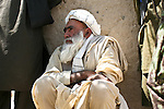 An elderly Afghan man listens as U.S. troops talk to villagers in the Arghandab valley near Kandahar, Afghanistan. The goal of U.S. forces is to help establish a lasting security presence in the Arghandab and win villagers over to the government side. But villagers say they've seen few tangible benefits from their government in the past nine years, and the Taliban remain a formidable presence in the valley. April 5, 2010. DREW BROWN/STARS AND STRIPES