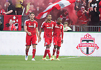 Toronto, Ontario - May 17, 2014: Toronto FC forward Jermain Defoe #18 and Toronto FC defender Bradley Orr #16 celebrate a goal with Toronto FC forward Luke Moore #27 during a game between the New York Red Bulls and Toronto FC at BMO Field. Toronto FC won 2-0.