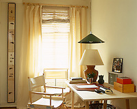 A simple home office takes advantage of a sunlit corner and a window dressed in bleached cotton curtains