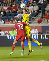 Columbus' Aaron Schoenfeld (34) heads the ball while being pressured by Chicago midfielder Logan Pause (12).  The Chicago Fire defeated the Columbus Crew 2-1 at Toyota Park in Bridgeview, IL on June 23, 2012.