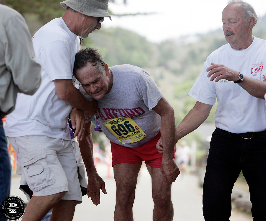 Philip Smith (696) of Sausalito is helped by  medical officials as he crosses the finish line with their assistance at the 99th running of the Dipsea Race at Sintson Beach State Park in Stinson Beach, Calif. on Sunday June 14th, 2009.