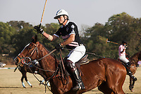 Western Australia Polo Team captain Greg Johnson rides forward at the start of the Royal Jaipur Polo Team (in pink) vs Western Australia Polo Team (in black) game during the Argyle Pink Diamond Cup, organised as part of the 2013 Oz Fest in the Rajasthan Polo Club grounds in Jaipur, Rajasthan, India on 10th January 2013. Photo by Suzanne Lee