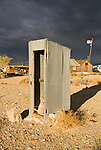 Corrugated outhouse, clouds, U.S. flag blowing in the wind at a ghost town in Nevada.