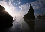 Oregon, South west, Bandon. A cyclist uses fat tires to ride through sand and surf at Face Rock Wayside at sunset in autumn.
