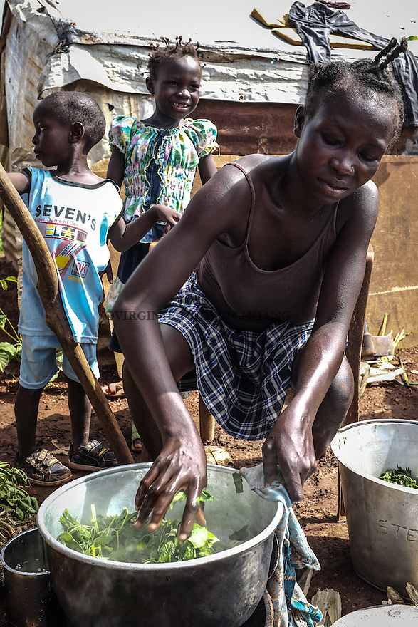 CAR, Bangui: A woman is cooking manioc in the Mpoko camp. The IDP's from the camp are cultivating their own gardens in order to have enough food.  17th April 2016.<br /> <br /> RCA, Bangui : Une femme fait cuire du manioc dans le camp Mpoko . Les d&eacute;plac&eacute;s  du camp cultivent leurs propres jardins afin d'avoir assez de nourriture . 17 avril 2016.