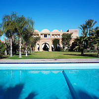 A view across the swimming pool and palm-filled lawn towards the house