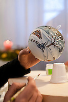 A winter scene is being painted on a large Christmas bauble